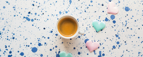 Wooden board with cup of espresso coffee on white and blue dots abstract background with white and green hearts. Valentine's mother day breakfast concept © tenkende