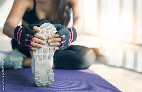 Sticker Fit woman stretching her leg to warm up at gym