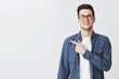 Leinwanddruck Bild - Polite and friendly handsome young caucasian man in glasses and blue shirt over t-shirt smiling joyfully as pointing left at copy space showing cool place for advertisement over grey wall