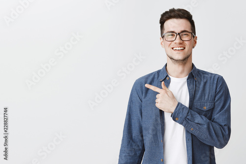 Leinwanddruck Bild Polite and friendly handsome young caucasian man in glasses and blue shirt over t-shirt smiling joyfully as pointing left at copy space showing cool place for advertisement over grey wall