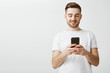 Leinwandbild Motiv Checking profile of girl he loves. Handsome delighted and happy caucasian guy with cool haircut and bristle holding smartphone looking at device screen with satisfaction reacting to daring message