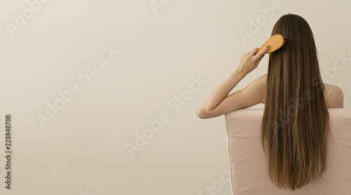 image of attractive woman brushing her  long hair, space for text