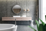 Sink and mirror in concrete bathroom, tub - 228855738