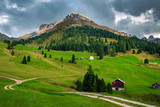 winding road through meadows with lonely houses in St. Maddalena in Italy - 228868130