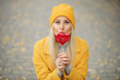 Fashion portrait pretty sweet young woman in yellow coat having fun with red lollipop heart over autumn street background