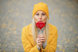 Fashion portrait pretty sweet young woman in yellow coat having fun with red lollipop heart over autumn street background - 228885769