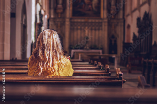 Young woman praying and meditating in church.