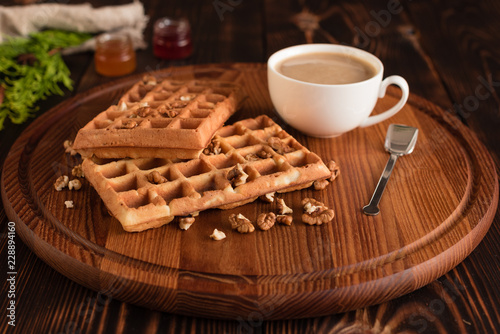 Poster Tasty fresh Vienna wafers, jam and cup of coffee on a dark wooden background