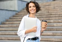 """Постер, картина, фотообои """"Beautiful woman walking outdoors holding laptop computer holding coffee."""""""
