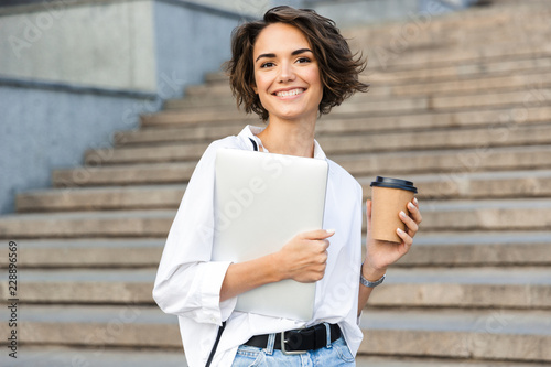 Poster Beautiful woman walking outdoors holding laptop computer holding coffee.