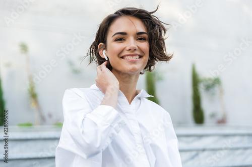 Attractive young woman in earphones - 228896780