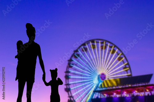 Leinwandbild Motiv Family silhouette in a theme park looking at the ferris wheel mother with her little daughter and baby