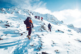 A group of climbers ascending a mountain in winter - 228904723