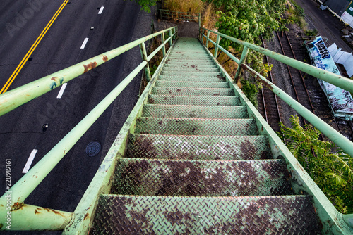 Green old rusted stairs going down onto the sidewalk next to the highway. View form above.