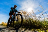 Cycling, mountain bikeing woman on cycle trail in autumn forest. Mountain biking in autumn landscape forest. Woman cycling MTB flow uphill trail. - 228940954