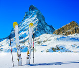 Ski in winter season, mountains and ski touring backcountry equipments on the top of snowy mountains in sunny day with Matterhorn in background, Zermatt in Swiss Alps. - 228943731