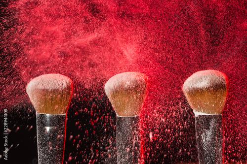 Leinwandbild Motiv Make up, beauty, mineral cosmetic concept - powder brush on black background with red powder splashed on it