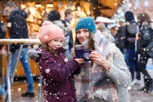 Leinwandbild Motiv Happy kid girl and young beautiful woman with cup of steaming hot chocolate and mulled wine. Adorable child and beautiful mum on Christmas market in Germany. Family walking on Xmas market.