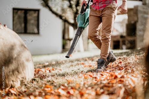 Leinwanddruck Bild Portrait of male using leaf blower, close up details of gardening