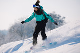 Woman snowboarder riding down from snowy hill - 228953372