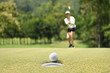 Leinwanddruck Bild - Woman golfer cheering after a golf ball on a golf green