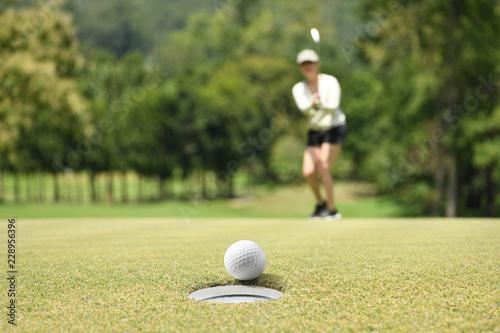 Leinwanddruck Bild Woman golfer cheering after a golf ball on a golf green