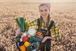 Leinwanddruck Bild - Harvest time in the country, woman farmer offering vegetables taking them to the market