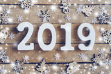 Wooden numbers forming the number 2019, For the new year and white snow with snowflakes on rustic wooden background. - 228973198