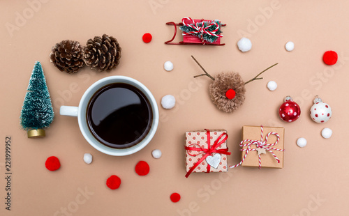 Leinwanddruck Bild Christmas ornaments with coffee cup on a light brown paper background