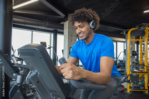 Sticker Handsome young african american man cycling at the gym