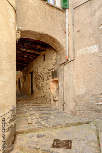 arched passage on narrow street with steps in village on Como lake, Moltrasio, Italy - 229022352