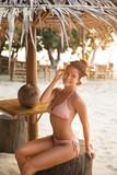 Sexy woman wearing bikini sitting in the beach bar