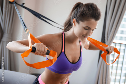 Wall mural Woman during her  workout at home with suspension straps