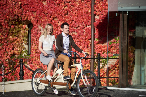 Poster Young smiling travelers couple, handsome bearded man and pretty long-haired blond woman cycling tandem bike on bright sunny day on background of brick building fully overgrown with red ivy leaves.