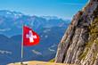 Leinwanddruck Bild - Swiss flag on Pilatus mountain with background alpine peaks