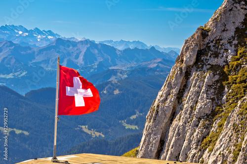 Leinwanddruck Bild Swiss flag on Pilatus mountain with background alpine peaks