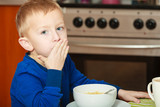 Kid boy eating breakfast, cereals and milk in bowl - 229065712