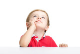 Llittle boy standing at white table looking up, isolated on a white background - 229069102