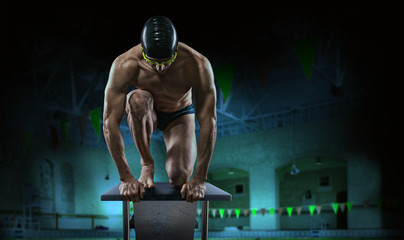 Swimming pool. Muscular swimmer ready to jump.