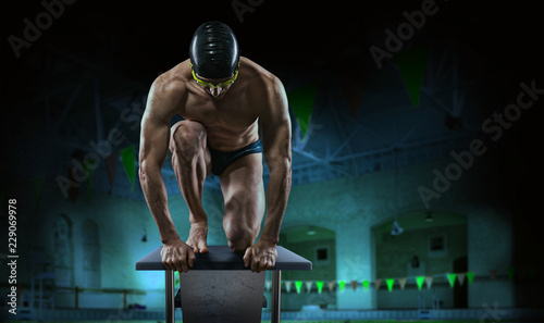 Swimming pool. Muscular swimmer ready to jump. - 229069978