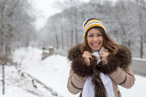 997ded46f11 Beautiful young woman standing outside in the snow in a forest smiling