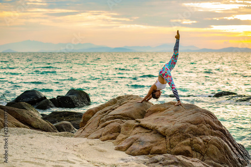 Poster woman playing yoga pose on sea beach against beautiful sun rising sky