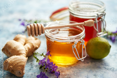 Healthy food table with different kinds of honey, fresh ginger and lime. Placed on stone table with copy space.