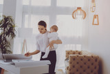 Successful mother. Successful working mother feeling busy standing near lamp in living room while holding her daughter - 229125746
