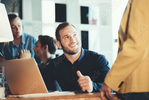 Leinwandbild Motiv Startup and millenial business concept. Man talking to team mate woman in office