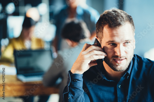 Leinwandbild Motiv Startup and millenial business concept. Portrait of young manager talking on the phone