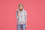 Portrait of young cheerful smiling woman in gray sweatshirt shy hello. - 229132386