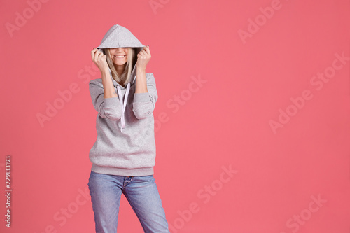 Girl closing her eyes with a hood smiles and standing on a bright pink background. Place to advertise