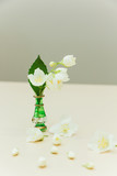 Jasmine flowers in a little green vase on a wooden background.