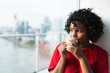 Leinwanddruck Bild - A close-up of a woman standing by the window drinking coffee.